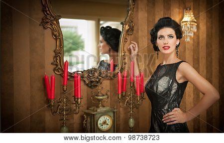 Beautiful girl in elegant black dress posing in vintage scene. Young beautiful woman