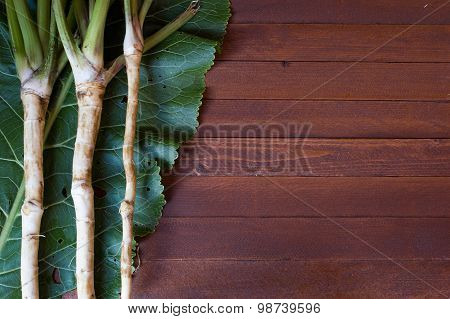 Fresh Horseradish Roots With Leaves On Wooden Background