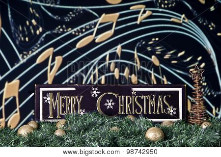 A black and gold Merry Christmas sign on a bed of garland and gold bulbs against a backdrop of musical staff and notes.