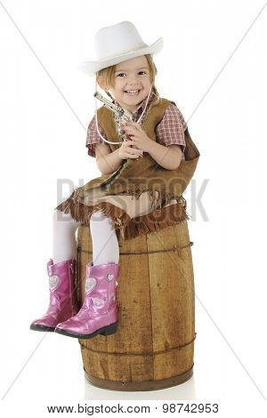 An adorable preschool cowgirl happily holding her gun while sitting on a rustic wood barrel.  On a white background.