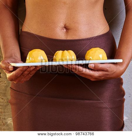 Dessert in hand at level of the abdomen.