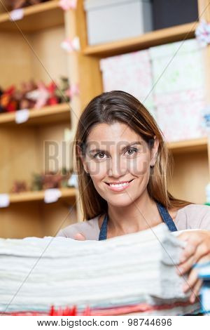 Portrait of smiling mid adult saleswoman with papers in shop