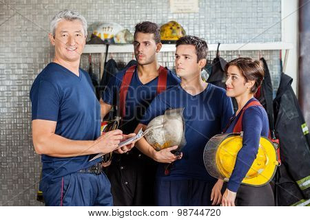 Portrait of happy mature fireman standing with team at fire station