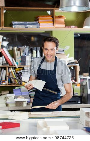 Portrait of smiling mid adult male worker holding papers and ruler at table in paper industry