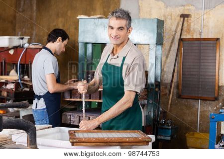 Portrait of smiling worker stirring pulp and water with stick while coworker using press machine in paper factory