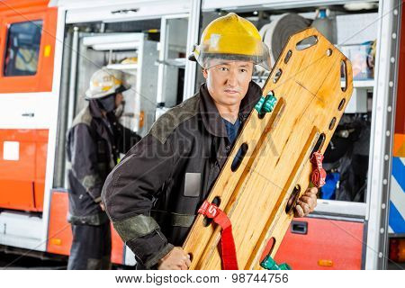 Confident male firefighter holding wooden stretcher against truck at fire station