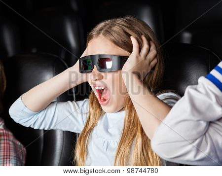 Scared girl screaming while watching 3D movie in cinema theater
