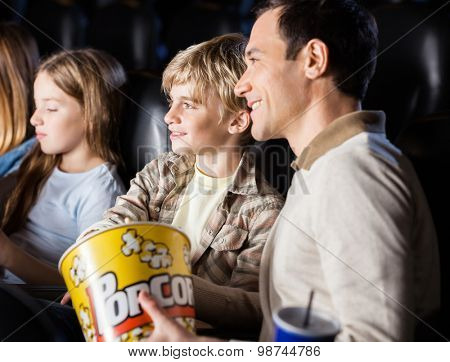 Family having popcorn while watching movie in cinema theater