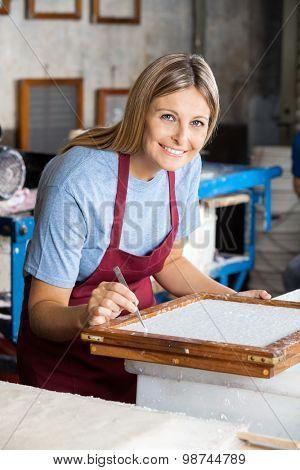 Portrait of mid adult female worker cleaning paper with tweezers in factory