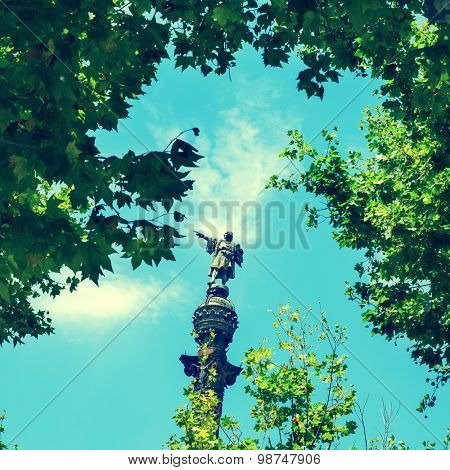 a view of the Columbus Monument in Barcelona, Spain, between some trees, with a retro effect