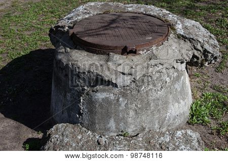 Manhole With The Cover On The High Concrete Basement