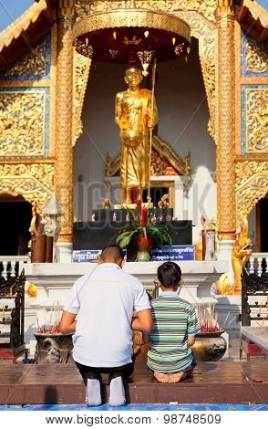 Father And Son Worshiping Buddha