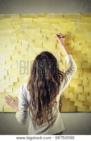Woman writing on a wall of post-it