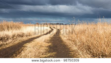 Dirt Road In The Dry Field In A Cloudy Day