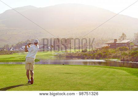 golfer hitting golf shot with club on summer vacation