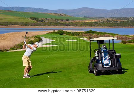 golf man playing shot with cart nearby on vacation