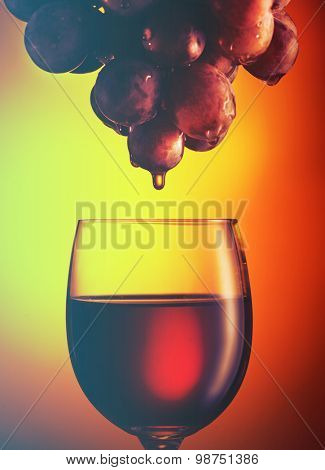 Wine glass with red wine and grapes. Filtered image: vintage effect.
