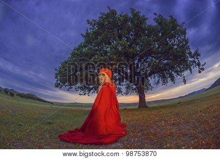 Beautiful Blonde Woman In Old-fashioned Dress And Red Cloak Sitting Under An Oak