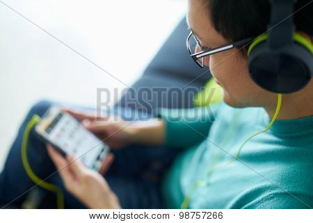 Asian Man With Green Headphones Listens Music Podcast Phone