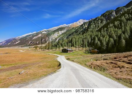 Wide dirt road in an Alpine valley. Sunny autumn day. Valley in the mountains of Austria