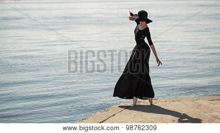 Ballerina In Hat And Long Black Dress Dance.