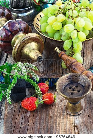 Hookah Amid Bunches Of Grapes And Strawberries