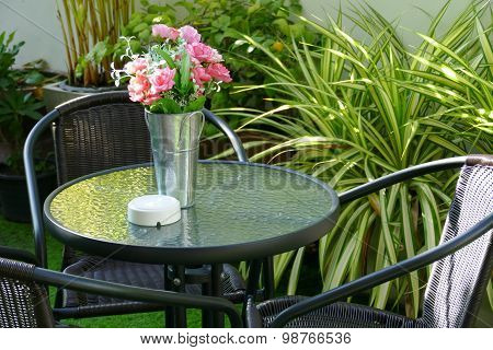 Black Rattan Chair, Desk And Fake Flower In The Vase