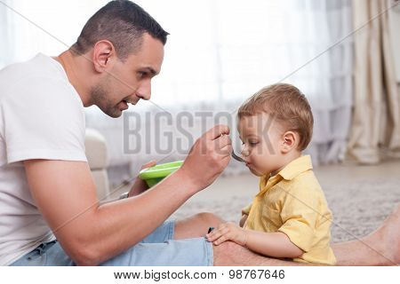 Attractive young man is caring his child