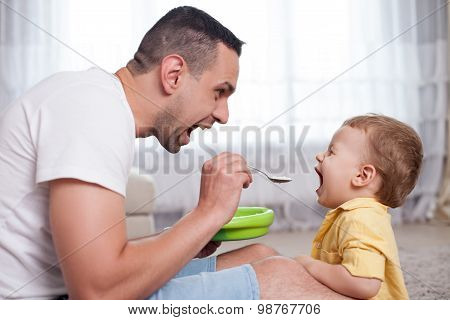 Handsome young man is feeding his child