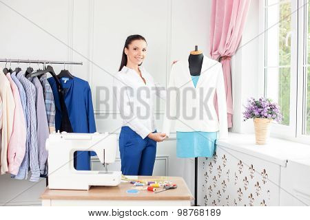 Attractive young fashion worker is projecting new clothing