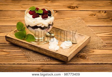 Eton mess - traditional english dessert with cream, berries and meringues on the wooden background.