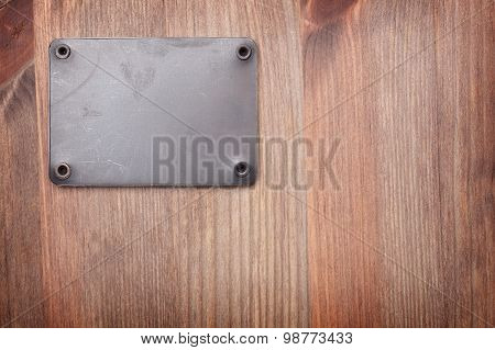 A Wooden Background With Metal Label