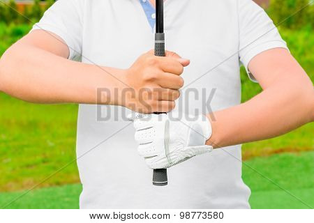 Men's Hands Hold The Putter Firmly On The Field Golf Course