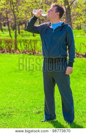 Vertical Portrait Of A Man Drinking Water On A Green Lawn