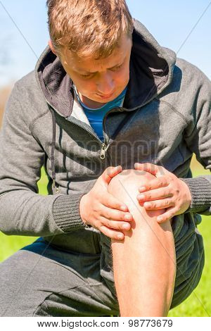 Athlete Inspects Diseased Knee While Jogging