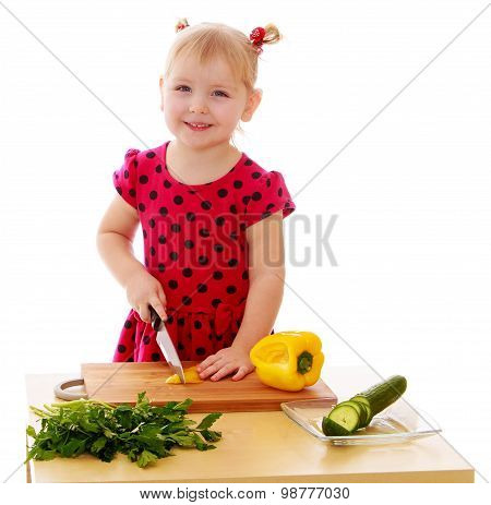 Little girl cut vegetables