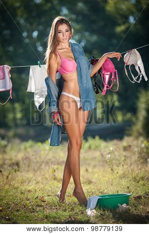 Sexy brunette woman in bikini and shirt putting clothes to dry in sun. Sensual young female