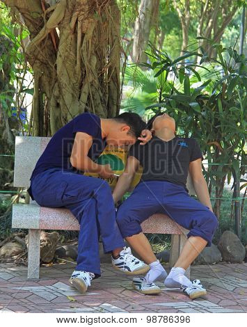two guys are resting on bench in park of Hanoi