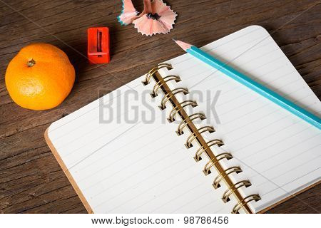 An opened notebook with pencil orange and Pencil Sharpener on old wooden table.