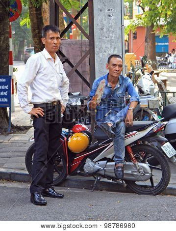 two men are waiting somewhat on the street in Hanoi