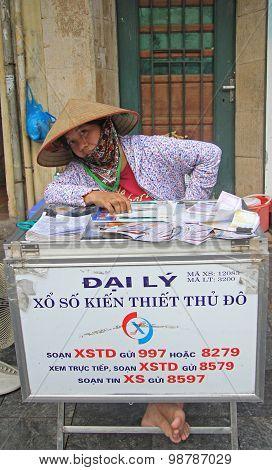 woman sells lottery tickets on streetin Hanoi