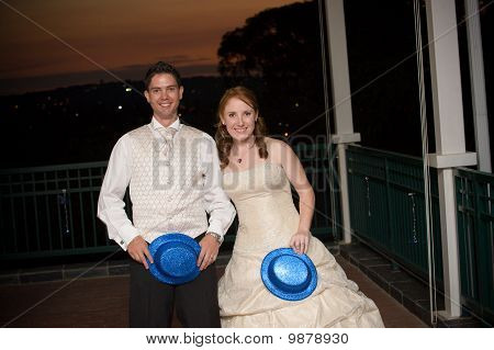 sexy bride and young handsome groom with blue hat outside