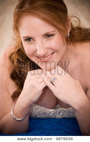 just married bride laying down with cleavage visible whilst smiling