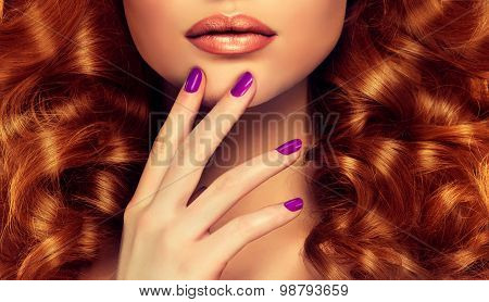 Girl with curly red hair and purple manicure