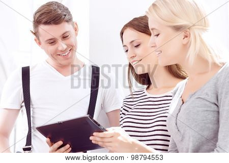 Cheerful students holding tablet computer