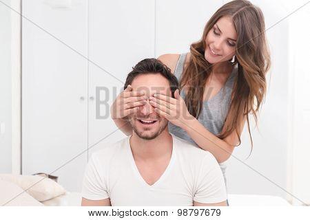 Beautiful girl closing eyes of boyfriend.