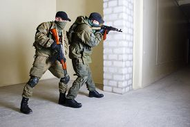 picture of ak-47  - insurgents with AK 47 inside the building - JPG