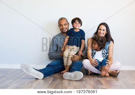 poster of Happy multiethnic family sitting on floor with children. Smiling couple sitting with two sons and lo