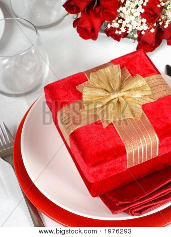 A Christmas Present In A Romantic Table Setting With Roses
