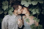Stylish Hipster Couple Kissing In Green Leaves, Holding Hands. Man And Woman Embracing, In Love Rela poster